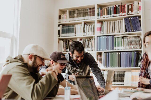 młodzi ludzie przedsiębiorcy wbiurze kancelarii rejestrują stowarzyszenie online porady pisanie nakomputerze umów